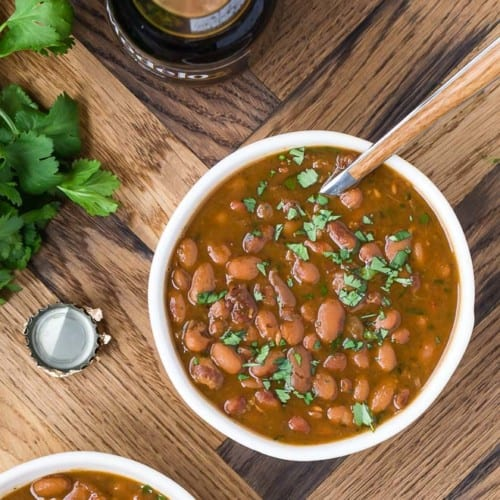 Image of two bowls of frijoles borrachos, both garnished with fresh cilantro.