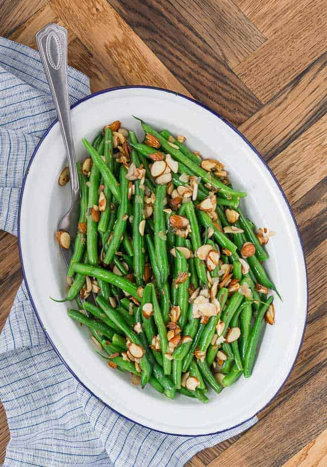 Image of perfectly cooked, bright green green beans on a white platter. They are cooked with toasted almonds and fresh lemon zest.