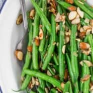 Image of green beans with lemon zest and almonds on a white and blue plate, with a serving utensil also pictured.
