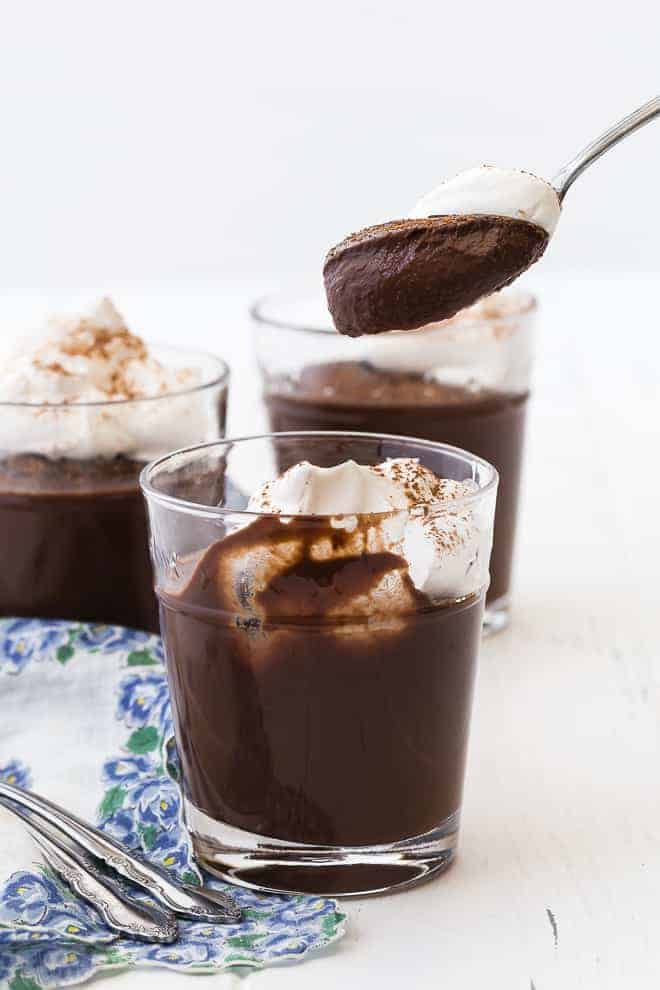 Image of chocolate pudding being scooped out of a small clear glass. It's topped with homemade whipped cream for the perfect bite.