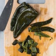 Image of roasted poblano peppers, two whole, one cut in a two different ways (strips, diced).