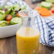 Image of red wine vinaigrette in a small jar. A tossed salad and chopped vegetables are pictured in the background.