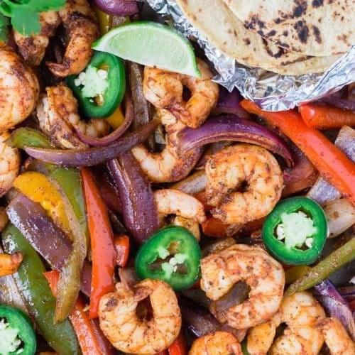 Colorful shrimp fajitas on a sheet pan with tortillas, limes, jalapeno, and cilantro.