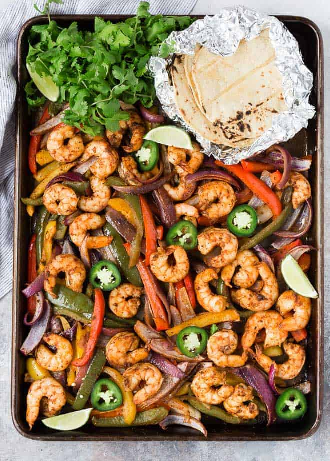 Sheet pan full of colorful vegetables and marinated shrimp.