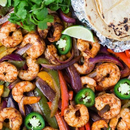 Image of colorful bell peppers and shrimp on a sheet pan with foil-wrapped tortillas, cilantro, lime and jalapeno.