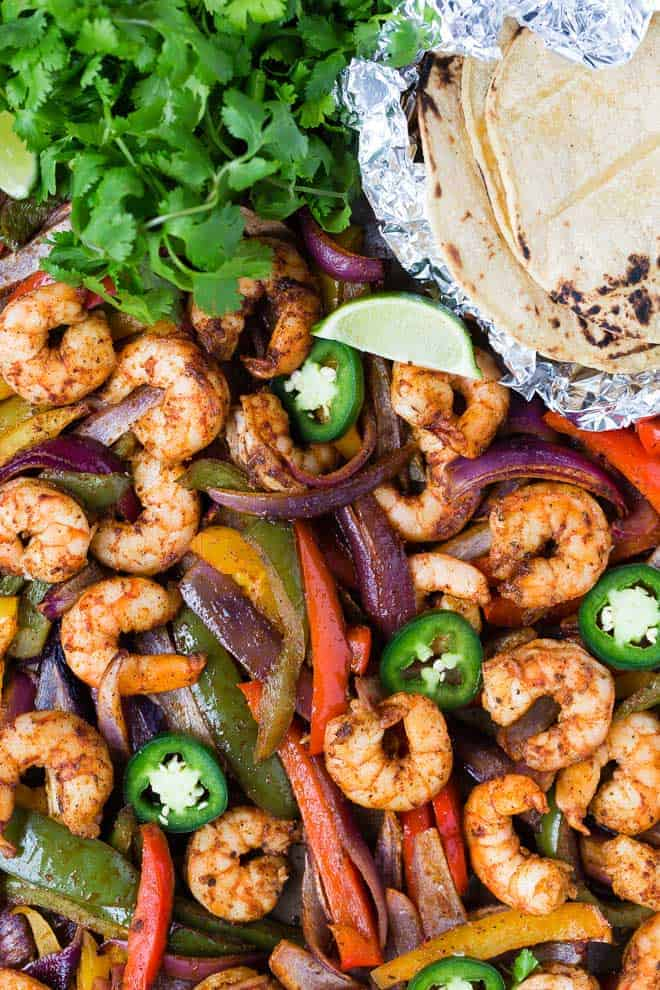 Colorful bell peppers and shrimp on a sheet pan with foil-wrapped tortillas, cilantro, lime and jalapeno.