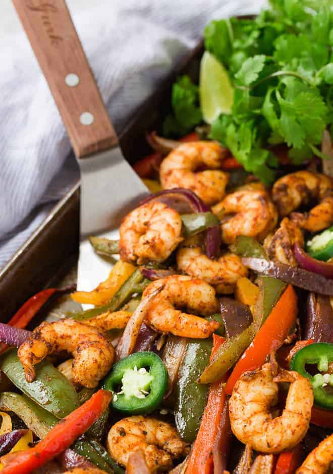 Sheet pan shrimp fajitas on a spatula.