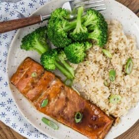 Image of glazed salmon on a plate with brown rice and broccoli. It's all garnished with sliced green onions.