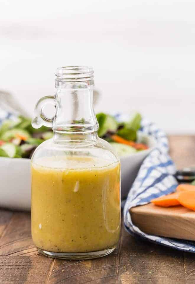 White wine vinaigrette in a small glass jar with a handle. A tossed salad is pictured in the background.