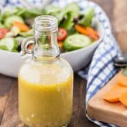 White wine vinegar salad dressing with a tossed salad pictured in the background of the photo.