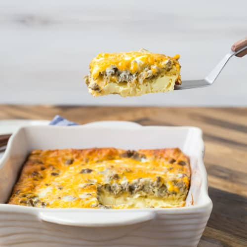 9x13 pan of breakfast casserole made with crescent rolls, one slice being lifted from the pan on a spatula.