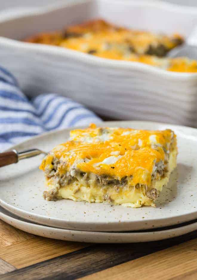 Slice of breakfast casserole on a plate. Layers of egg, crescent roll, sausage, and cheese are visible.