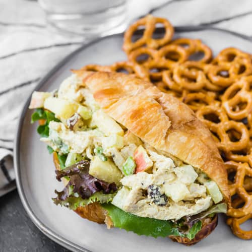 Close up image of chicken salad made with yogurt, curry powder, apples, raisins, and green onions on a fresh bakery croissant.
