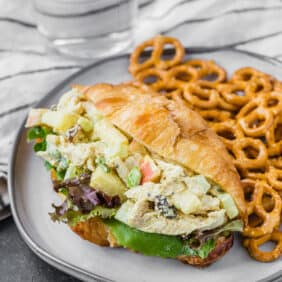 Image of healthy curried chicken salad on a croissant with fresh greens.