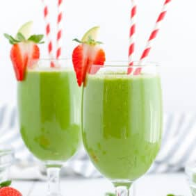 Two green drinks in stemmed glasses with red and white paper straws. Strawberries garnish the edge of the glasses.