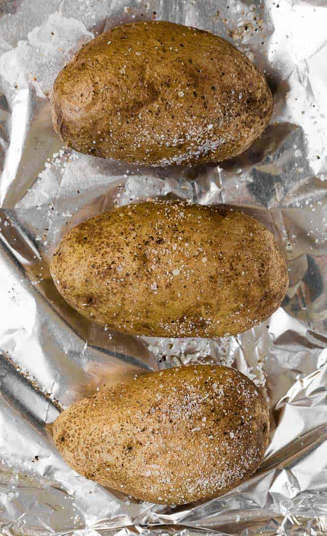 Image of three baked potatoes on a foil lined baking sheet. They are sprinkled with salt and pepper.