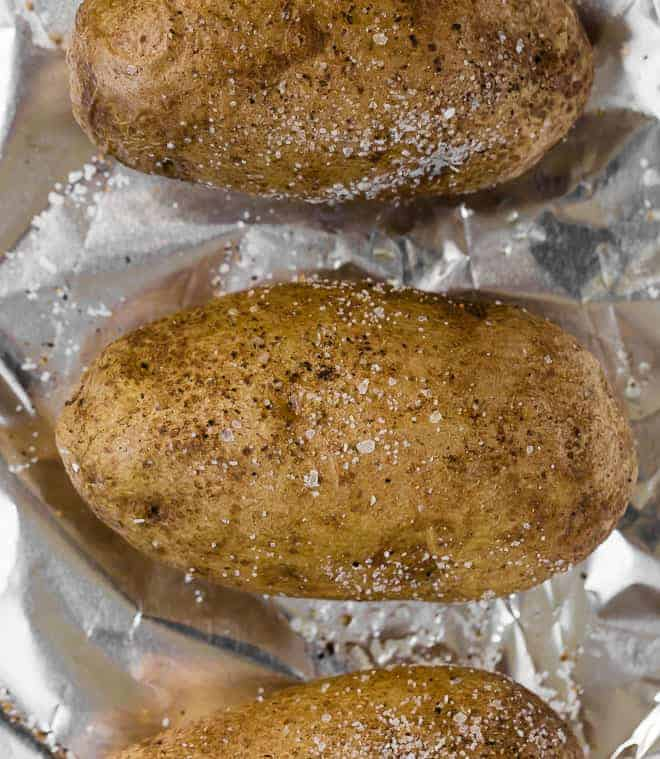 Image of baked potatoes on a foil-lined baking sheet.