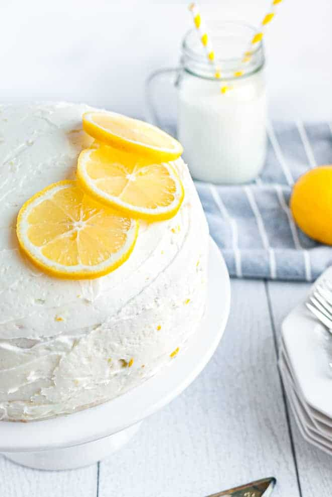 Lemon layer cake on a white cake stand topped with three lemon slices. In the background, milk, plates and additional lemons are pictured.