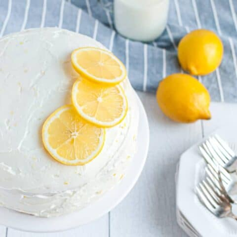 Image of white cake from above, topped with cream cheese frosting and three lemon slices.