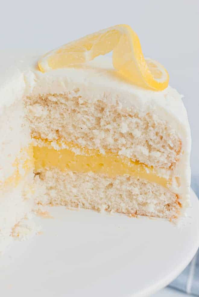 White cake with lemon filling and a lemon twist on top. It is placed on a white cake stand.