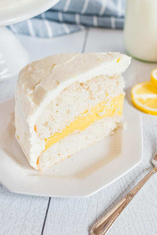 Slice of white layer cake with lemon filling and lemon cream cheese frosting. A glass of milk, a lemon slice, and a fork are also in the image.