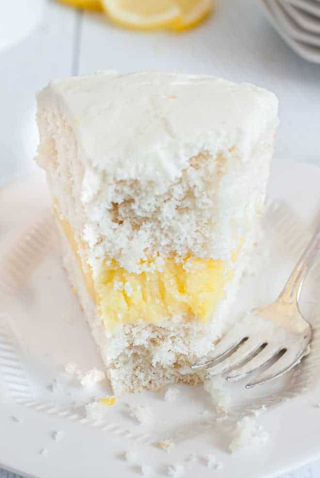 Slice of white cake with lemon filling and white frosting made with cream cheese and lemons, with a bite taken out of it. A fork is also pictured, resting on the plate.