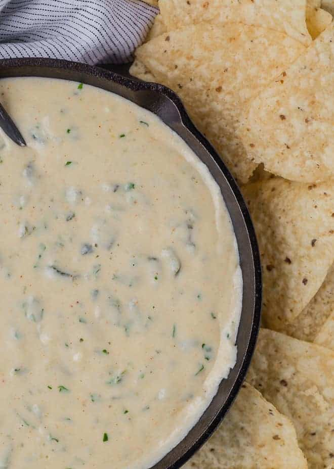 Close up overhead view of queso in a black skillet, next to a pile of chips.