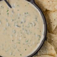 White queso dip in a black skillet, with a black spoon. Queso is studded with green poblano peppers and fresh cilantro, and placed next to tortilla chips.