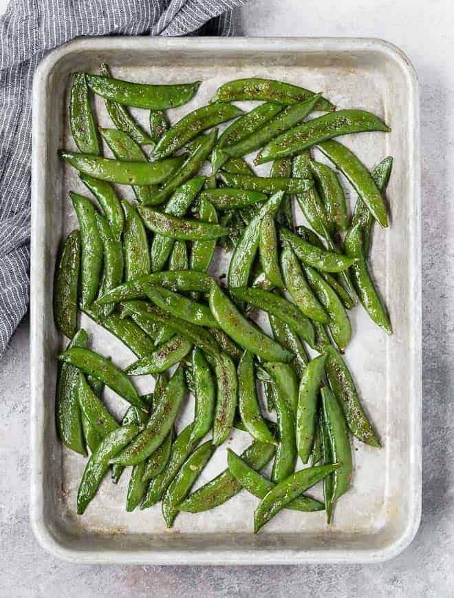 image of roasted sugar snap peas on a baking sheet.