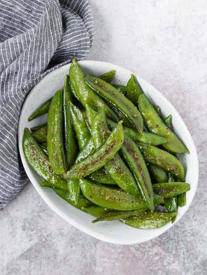 Image of roasted sugar snap peas in a small bowl.
