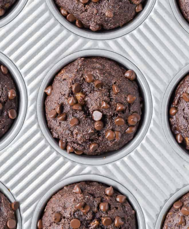 Overhead view of a close up of a chocolate muffins with chocolate chips.