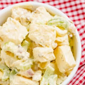 Close up overhead view of a bowl of diced potatoes, celery, onion, bacon, and boiled eggs tossed in a creamy light yellow dressing with flecks of green.