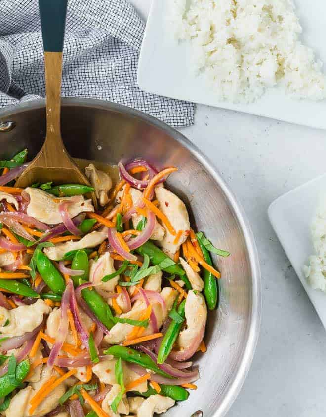 Overhead view of a wok filled with white rice, chicken, sugar snap peas, carrots, and red onions in stir fry form. It is garnished with fresh basil ribbons.