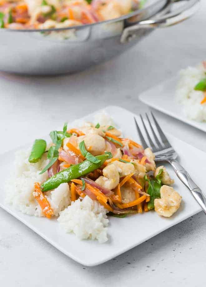 White plate filled with white rice, chicken, sugar snap peas, carrots, and red onions in stir fry form. It is garnished with fresh basil ribbons.