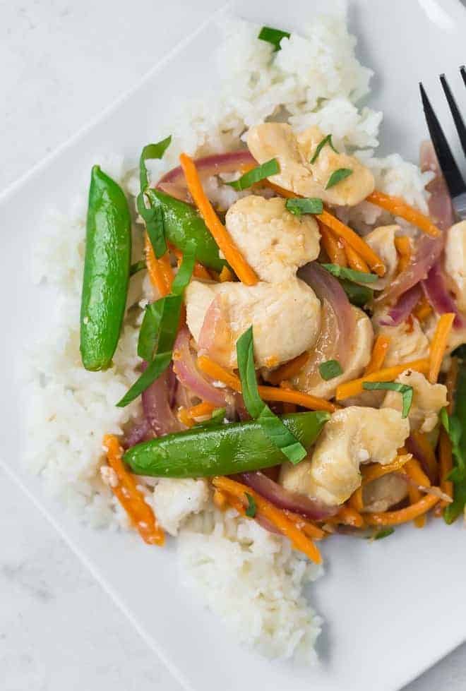 Overhead view of a white plate filled with white rice, chicken, sugar snap peas, carrots, and red onions in stir fry form. It is garnished with fresh basil ribbons.