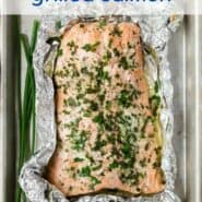 """Overhead view of grilled salmon in a foil pack. Text overlay reads """"garlic butter grilled salmon."""""""