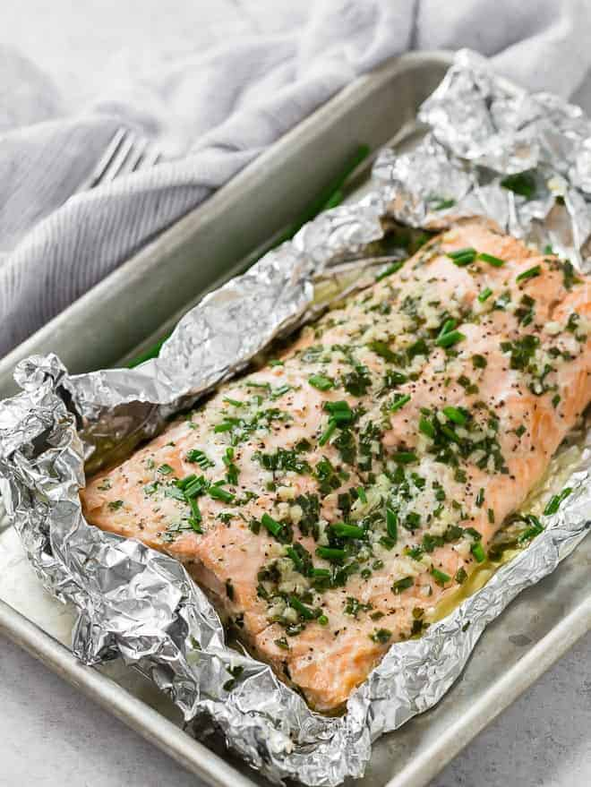Salmon partially wrapped in foil covered with chives and minced garlic.