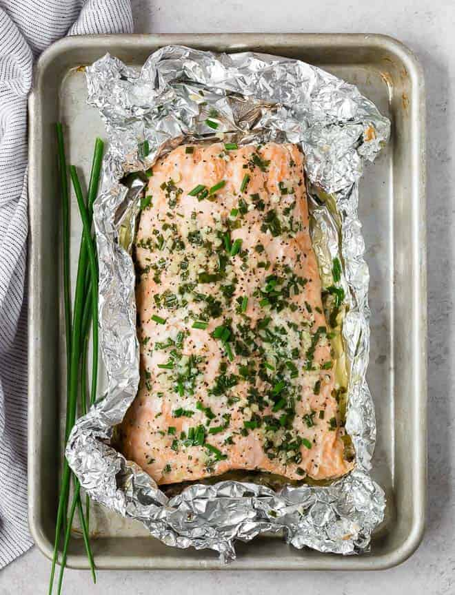 Overhead view of salmon surrounded up foil and on a sheet pan. Salmon is covered with chives and garlic butter.
