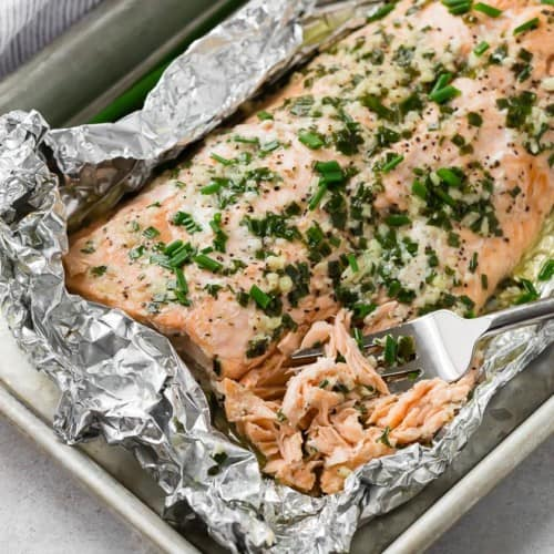 Foil-wrapped salmon that has been topped with chives and garlic, being flaked with a fork.