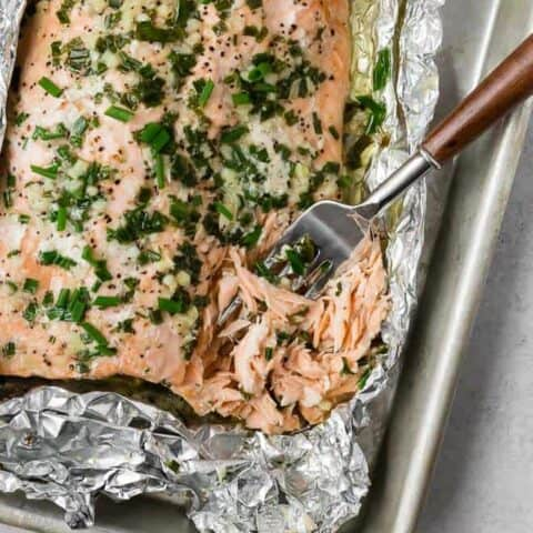 Overhead image of flaky salmon topped with garlic and chives. A fork is flaking the salmon.