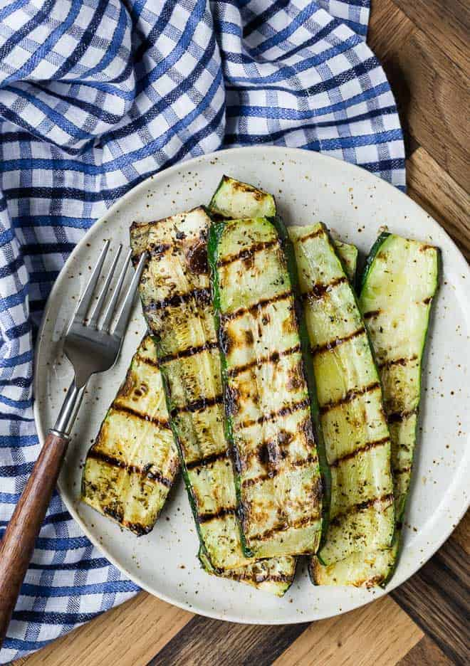 Overhead view of a earth-tone plate full of slices of grilled zucchini. A fork and a blue and white linen are also pictured.