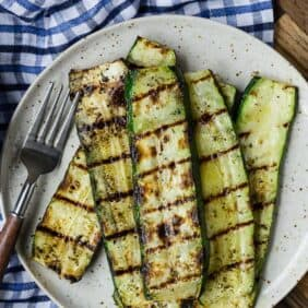 Overhead view of a plate of zucchini slices that have been grilled.