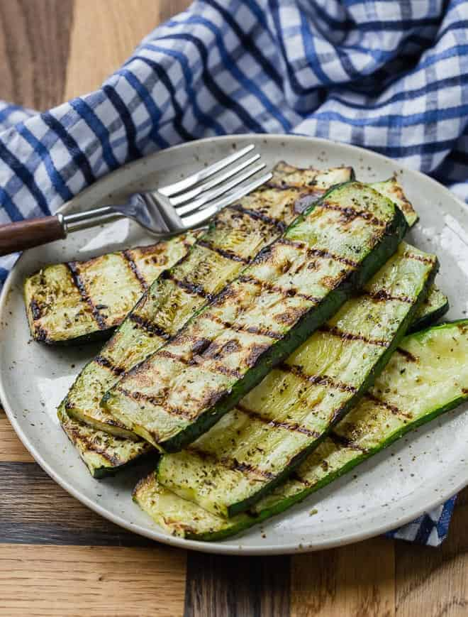 An earth-tone plate on a wooden background with a blue and white linen. The plate is full with grilled zucchini slices.