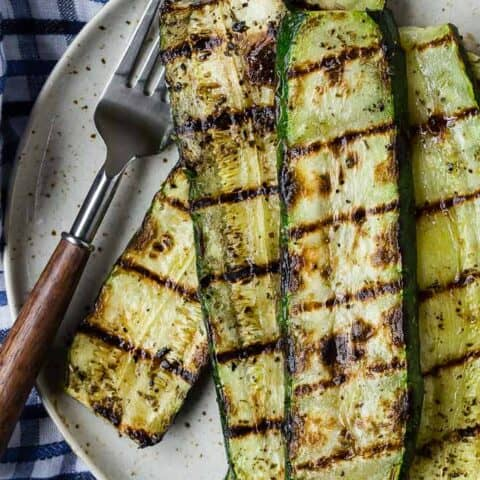 Overhead view of long slices of zucchini with grill marks. A fork and a blue and white linen are also pictured.