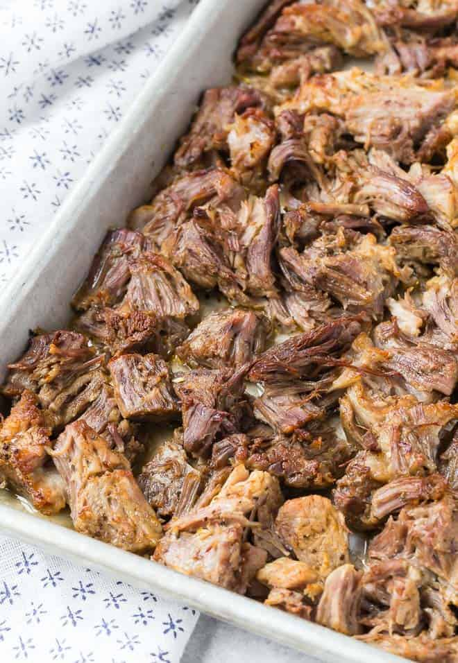 Close up view of pork carnitas that have become golden brown and crispy under a broiler.