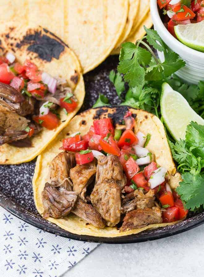 A black platter with two tortillas filled with pork carnitas and pico de gallo. Additional tortillas and pico de gallo are also visible.