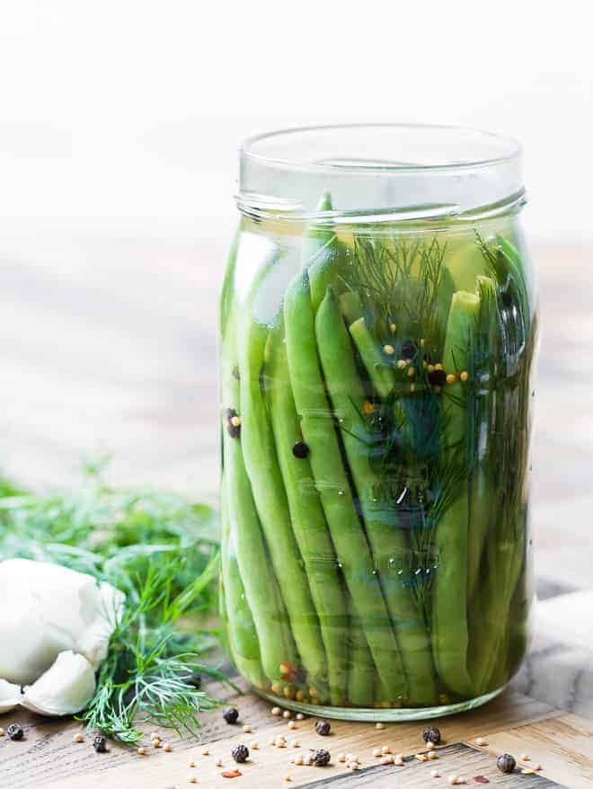 Large glass jar full of pickled green beans on a wooden surface. Dill, garlic, and spices are also pictured.