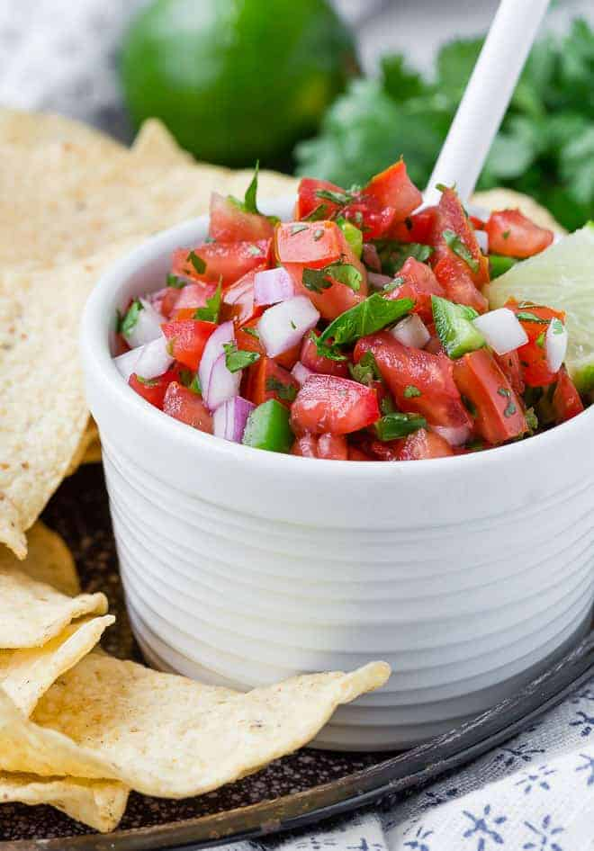 A small white bowl full of homemade pico de gallo, with a white spoon. The bowl is surrounded by chips, and a lime and fresh cilantro are visible in the background.