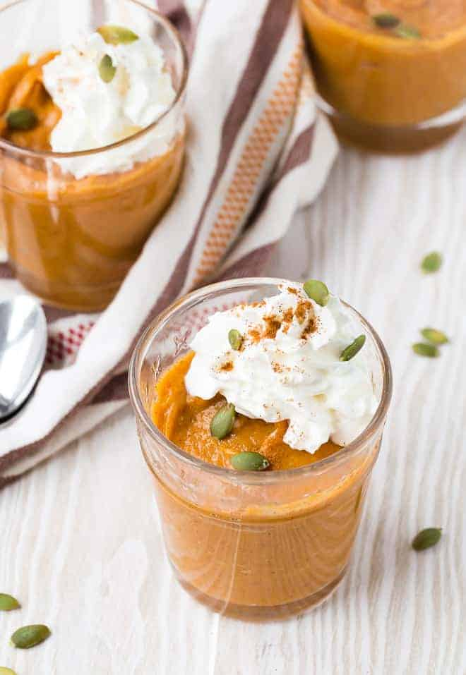 Three small glass dishes filled with orange pumpkin pudding, topped with whipped cream and garnished with pepitas and cinnamon.