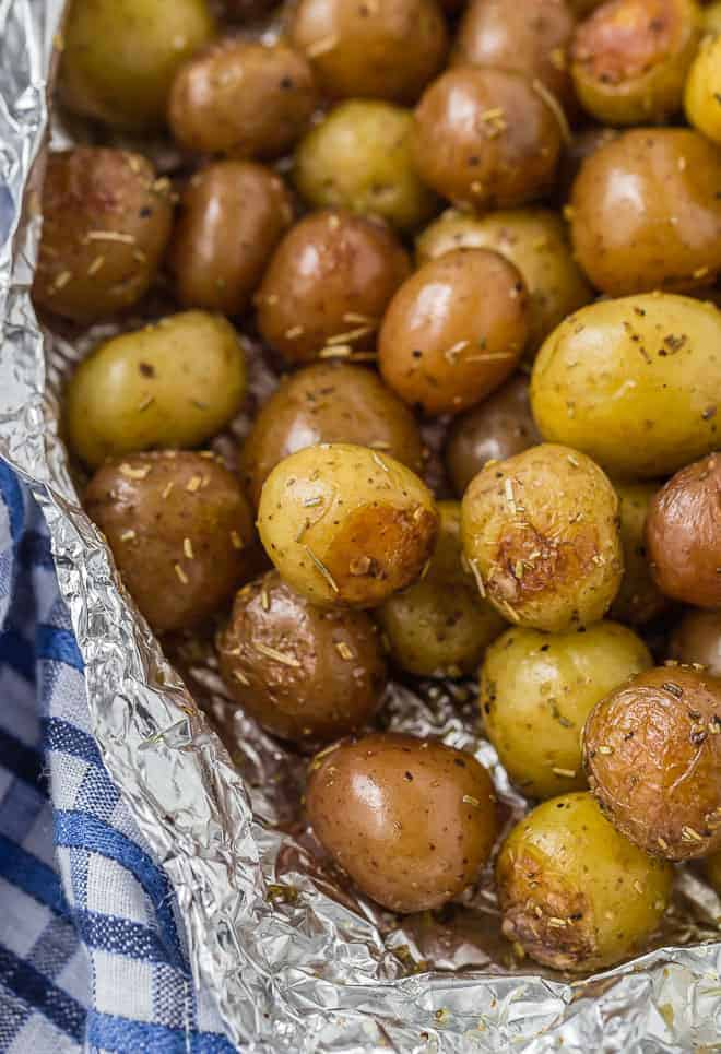A pound and a half of baby potatoes, partially wrapped in foil. Specks of rosemary are pictured, as well as a blue and white linen.